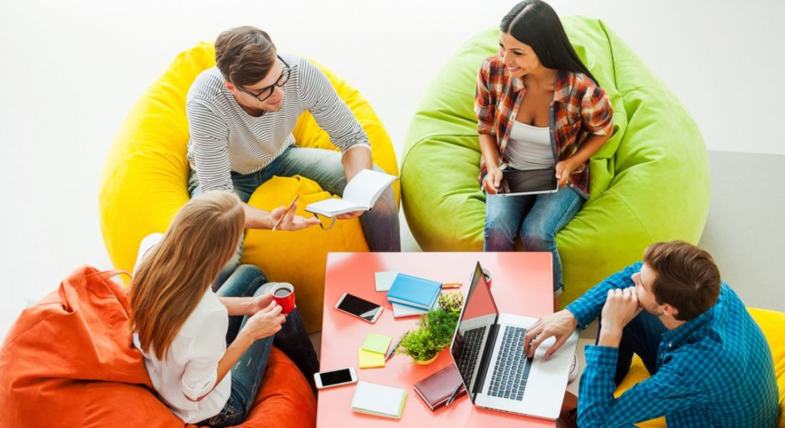 Top view of four young people working together, successfully using productivity tips while sitting at the colourful bean bags