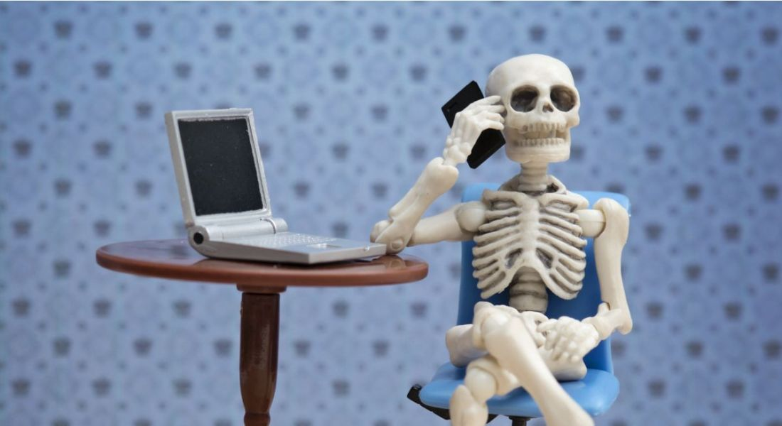 Toy skeleton sitting at a desk with a laptop, talking on a smartphone to depict overworking.