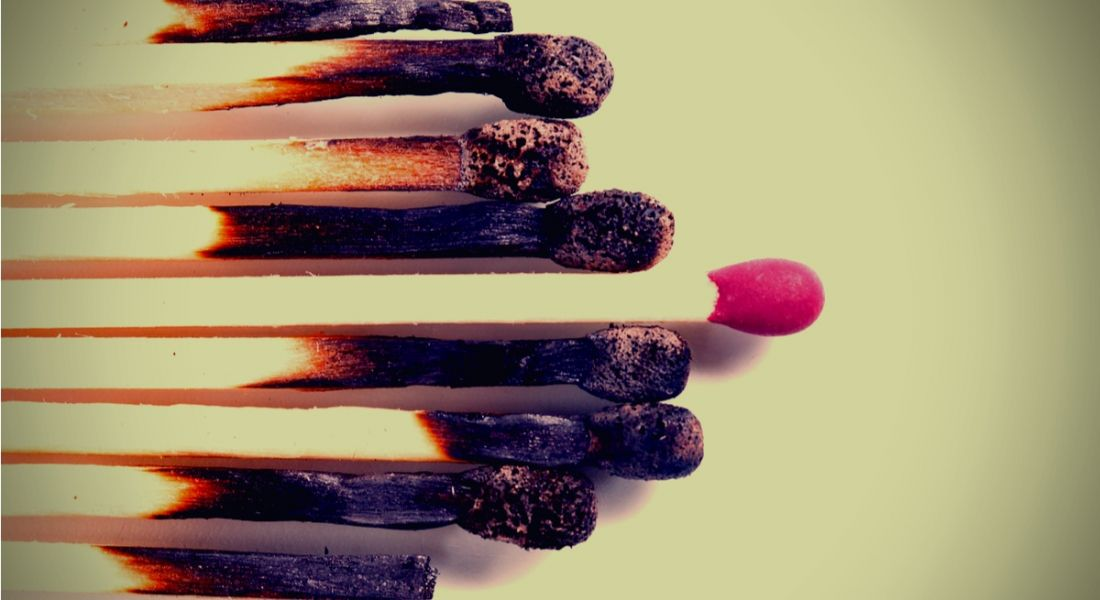 A row of burnt out matches, with one in the centre that has managed to not be burned depicting how to stay focused and avoid burnout.