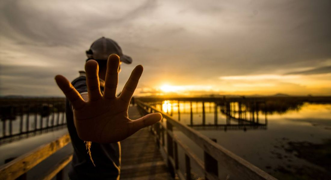 Man holding p 5 fingers at Sunset on pier. 5 ways inspirefest will inspire your career