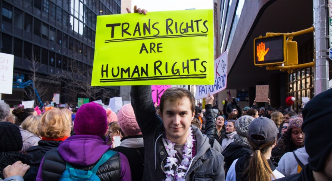 A man wearing a lei garland stands amid a crowd of women in New York holding a brightly coloured protest sign that reads 'trans rights are human rights'