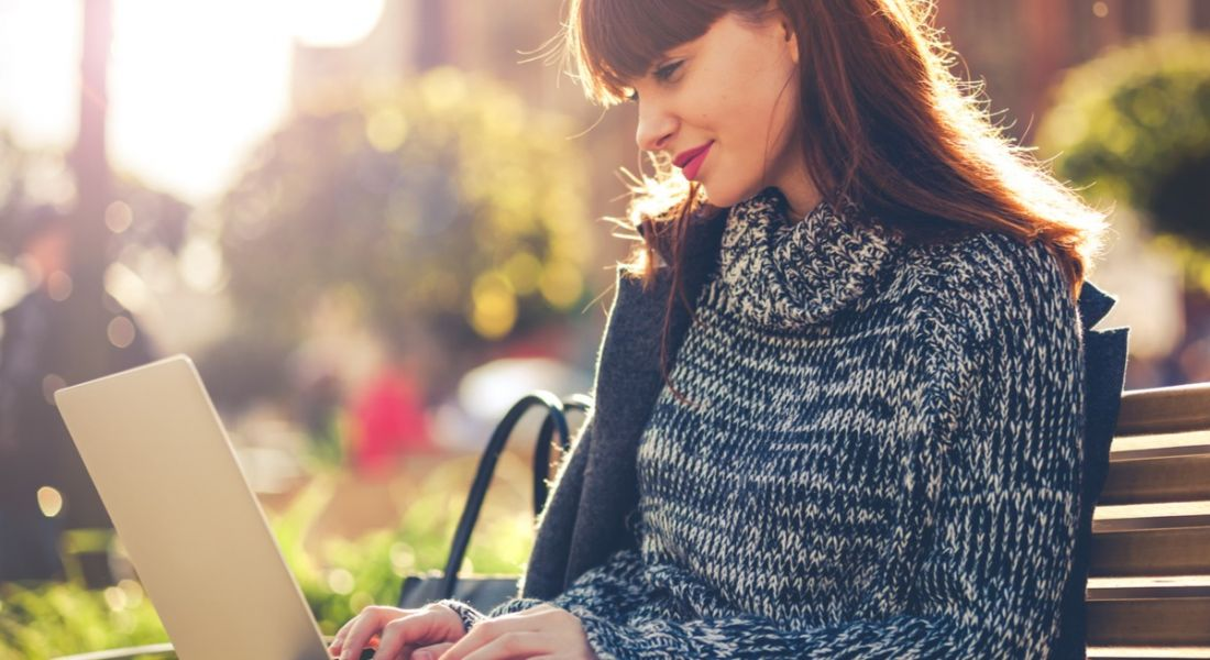 Woman on laptop in urban park, how to master your digital first impression