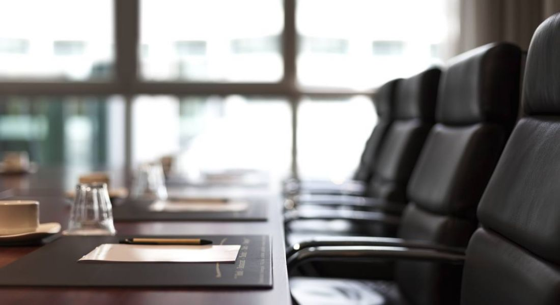View of a meeting agenda sitting on a table lined with leather swivel chairs.