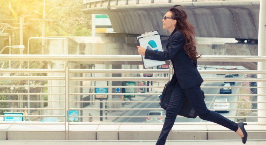 Young woman running with a folder, representing graduates rushing into their first job offer