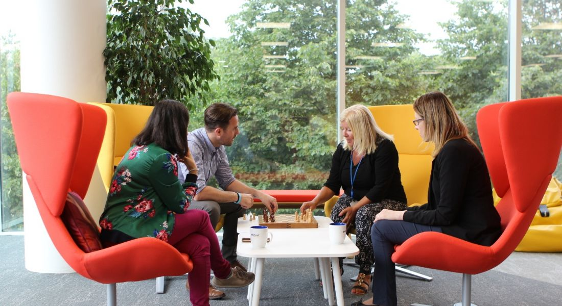 Four Workhuman employees sitting in colourful chairs playing chess