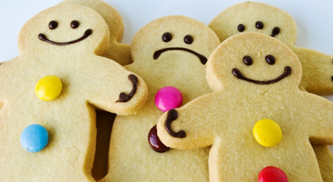A group of smiling gingerbread men, but one among them is sad, clearly suffering from imposter syndrome.