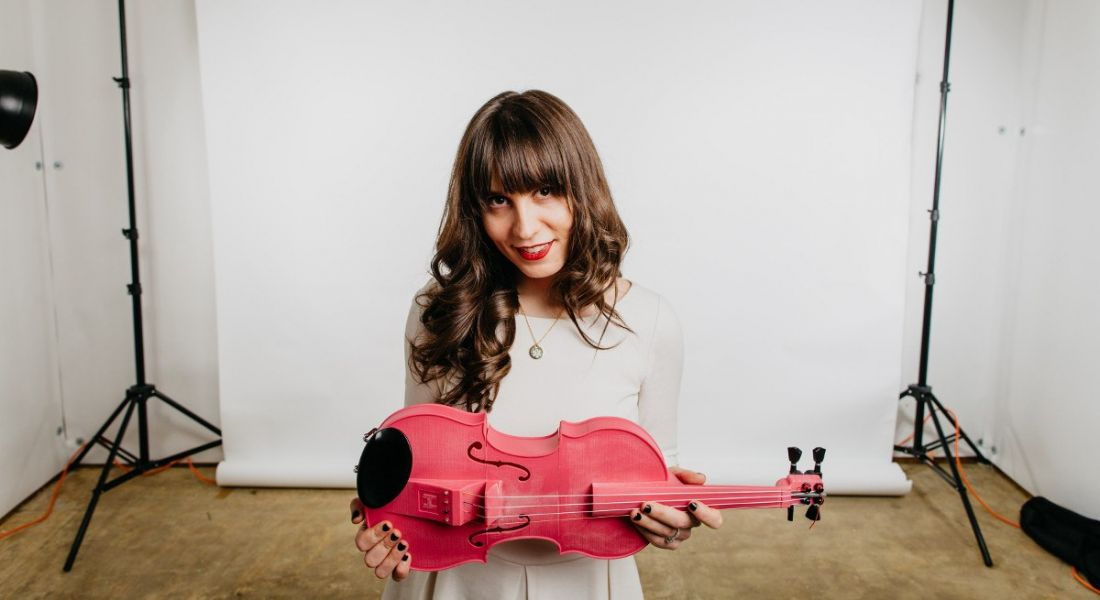Kaitlyn Hova holding a pink violin.