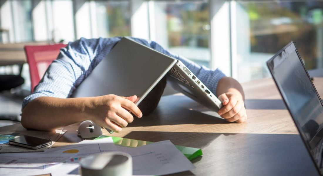 Man with laptop on top of head, such is the extent to which he is disengaged at work