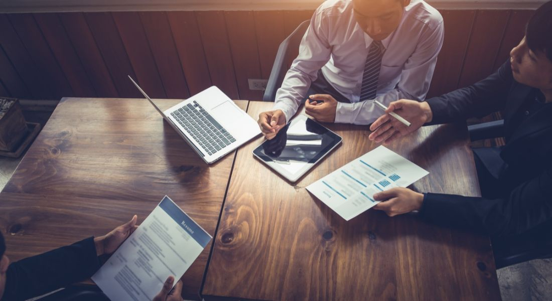 Businessmen at a mahogany table holding a job interview using laptop, iPad, and papers. Jobseekers need to be aware of these emerging industry trends