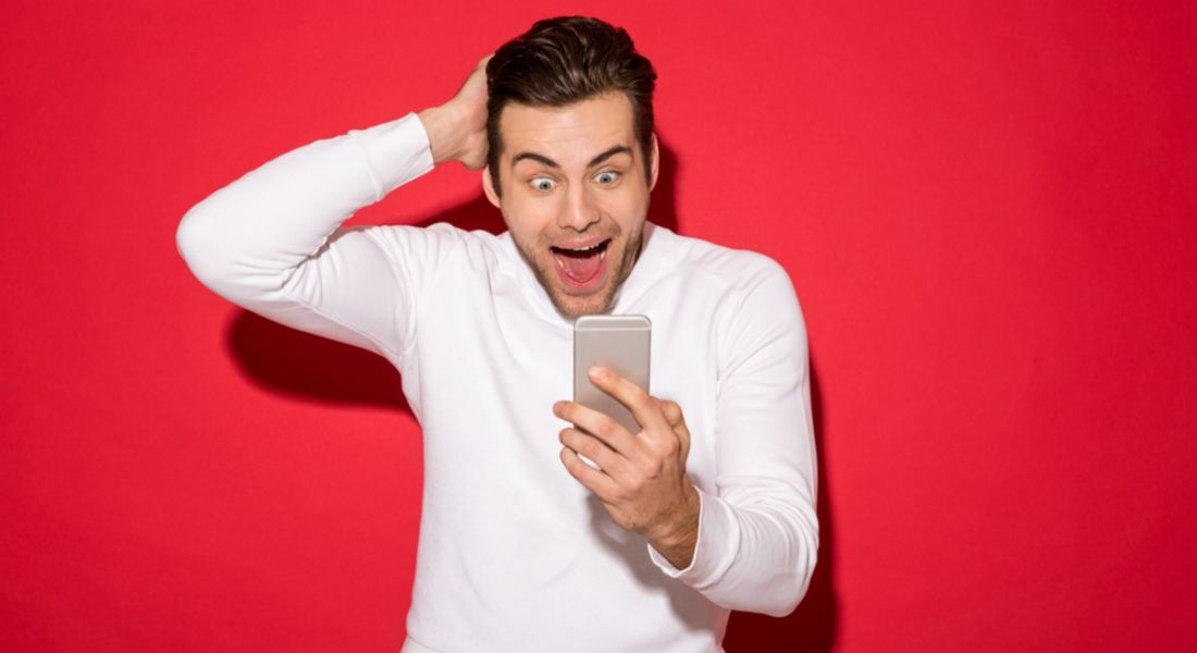 Man looking surprised at phone because of the amount of jobs advertised
