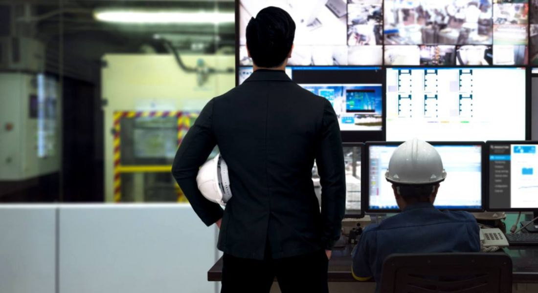 Process control room and industrial automation. One man sitting one man standing looking at array of screens. Robotics automation