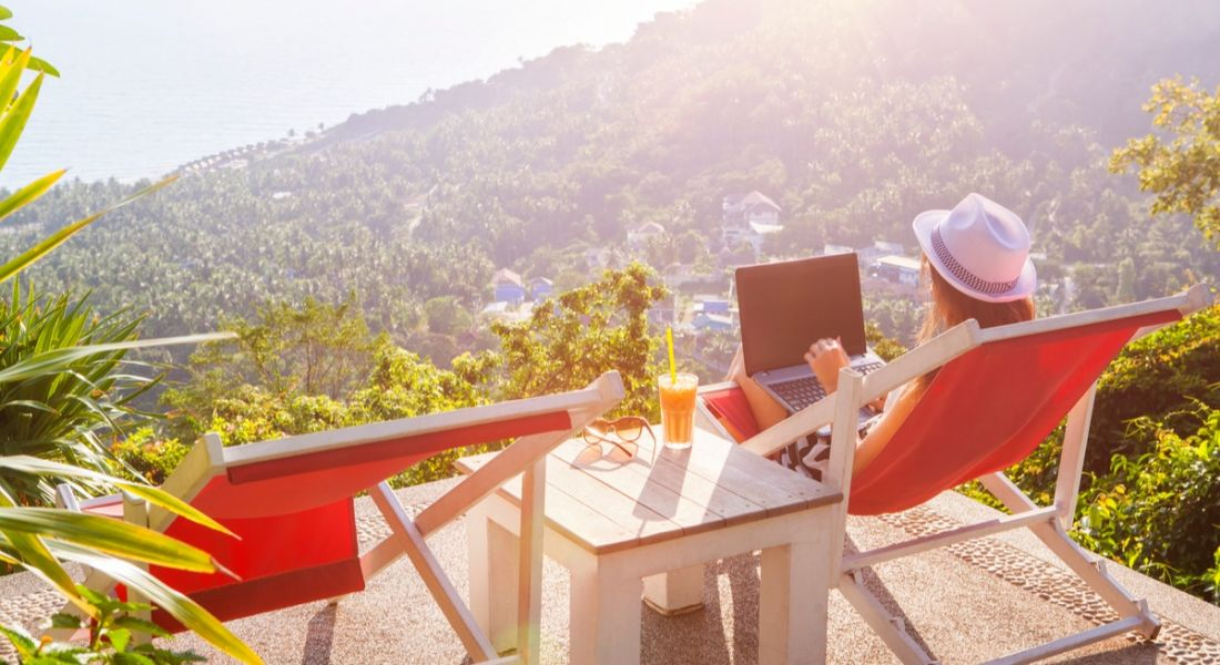 Girl working outside on laptop overlooking mountain view