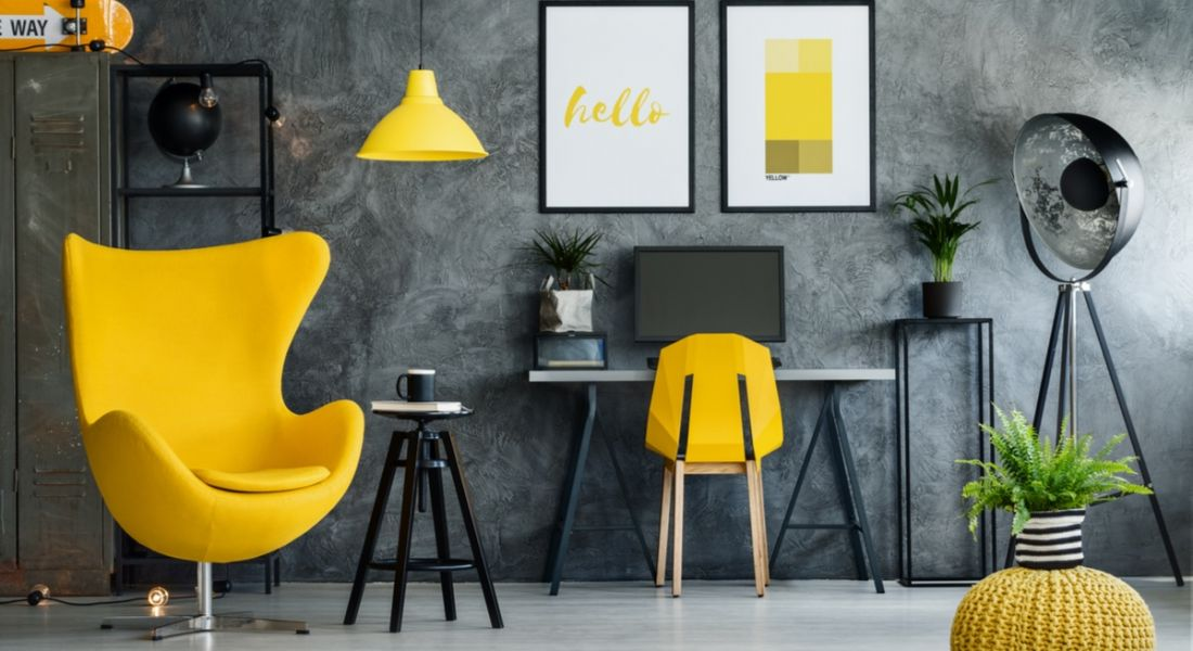 Cool charcoal grey office space with canary yellow arm chair at the left, yellow desk chair and yellow pictures on the wall.