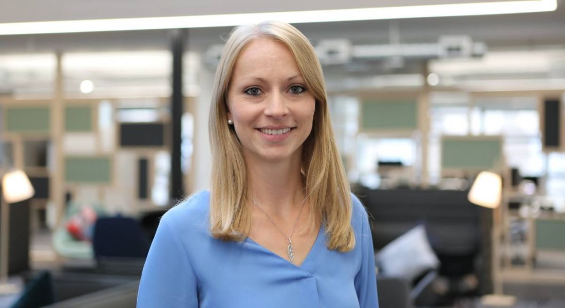 Blonde smiling woman in a light blue shirt smiling with the New Relic open plan office behind her.