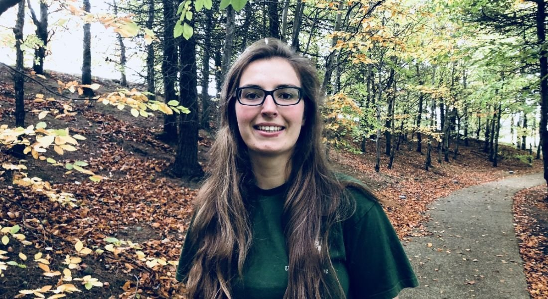 A young woman with long brown hair and glasses standing against the backdrop of a forest during autumn.