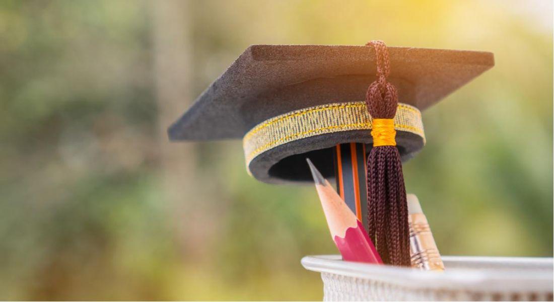 A mini graduation cap sitting on top of a pencil in a jar representing graduate programmes