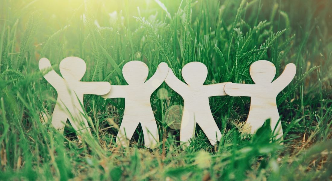 Wooden figurines standing in grass, holding hands symbolising HR companies working together to make the world better.