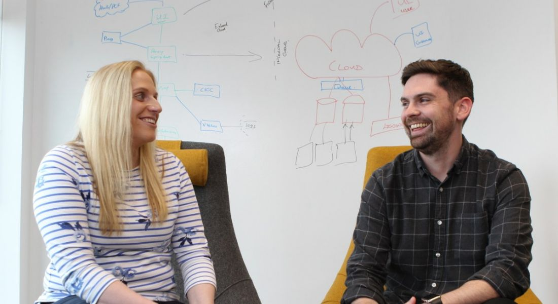 A young blonde woman and a young dark-haired man sitting in front of a whiteboard, laughing and discussing whiteboarding.