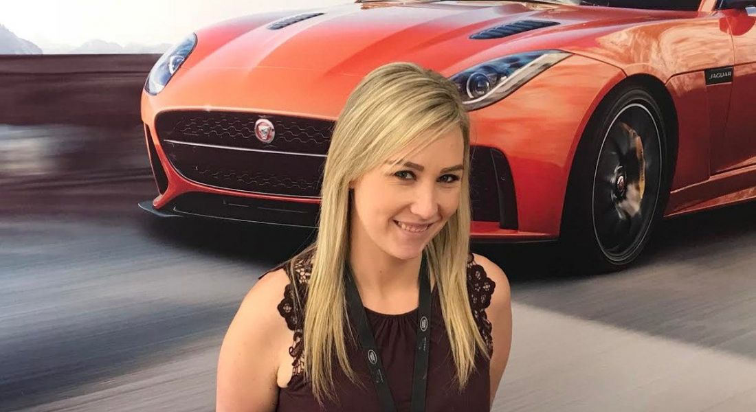 A young blonde woman smiling at the camera against wallpaper depicting a speeding sports car.