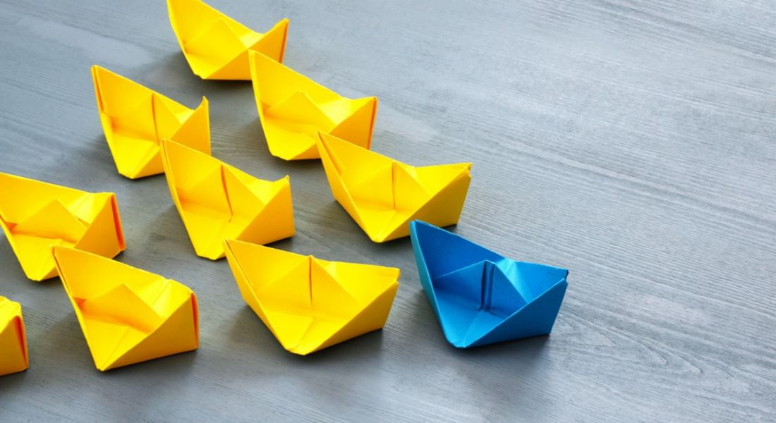 A blue paper sailboat leading a bunch of yellow paper sailboats on a wooden surface to represent leadership skills.