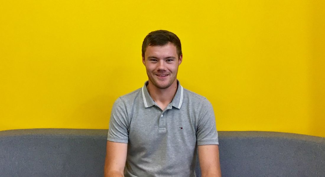 A smiling young man wearing a grey shirt staring directly ahead. He is sitting on a dark grey couch against a yellow wall.