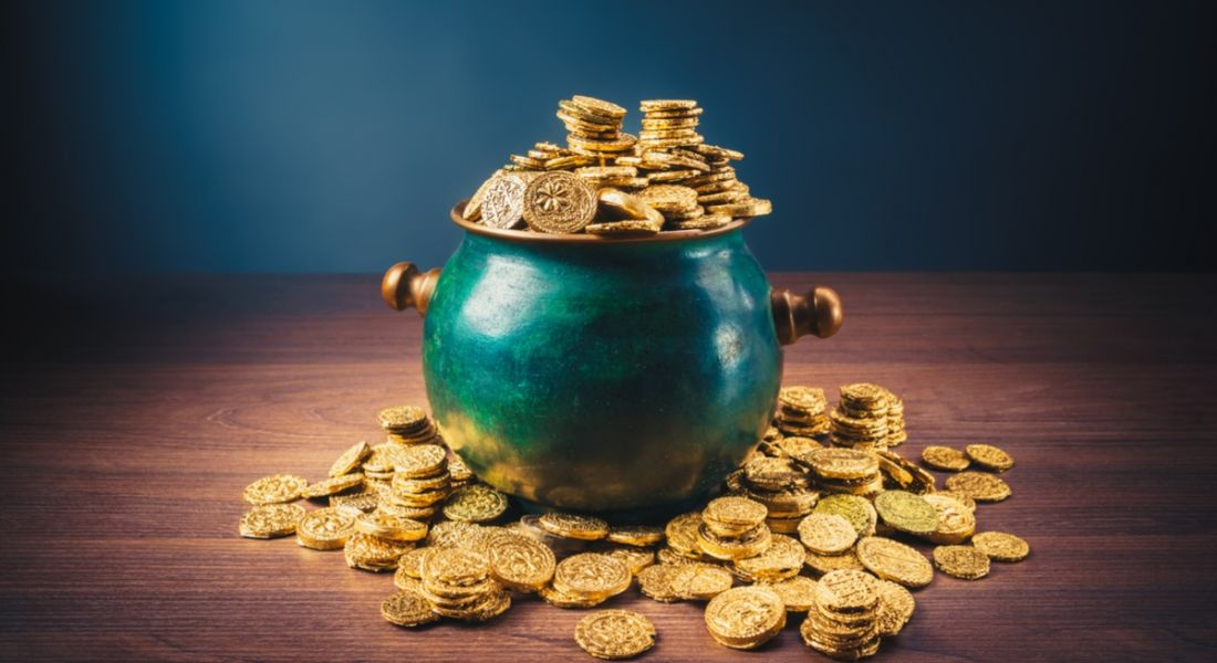 A green pot of gold coins overflowing onto a wooden table representing a bigger salary.