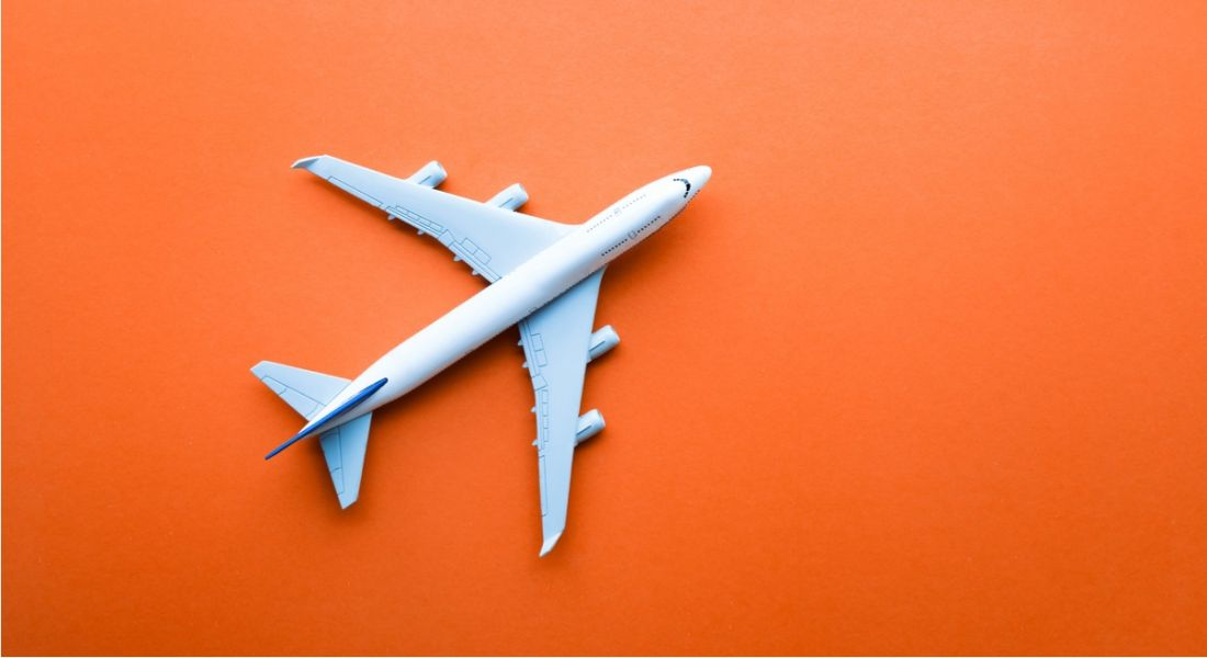 Aerial view of a toy aeroplane on a bright orange background.