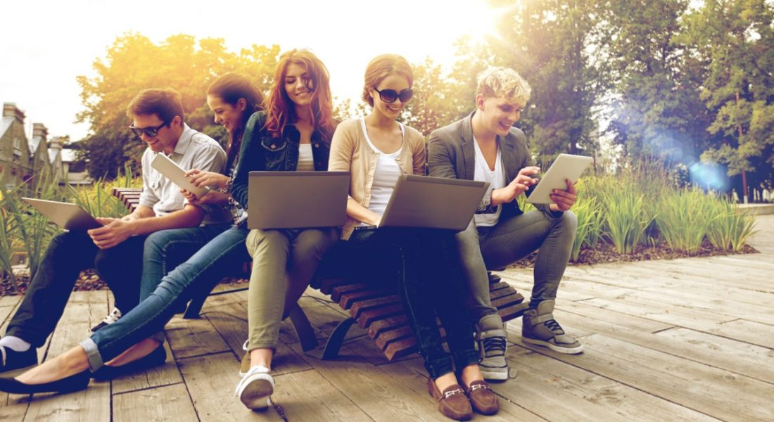 A diverse group of young graduates sitting on outdoor benches looking at their laptops on an overcast summer day.