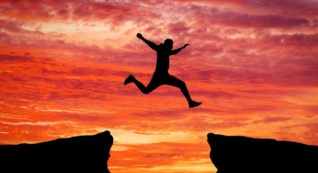 Man jumping over chasm against ruby sunset. Is the tech talent gap actually getting worse with time?