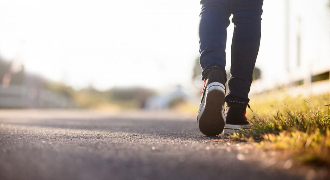 Close-up of the back of a person's feet as they walk down an empty road. They are wearing dark blue jeans and black Converse.