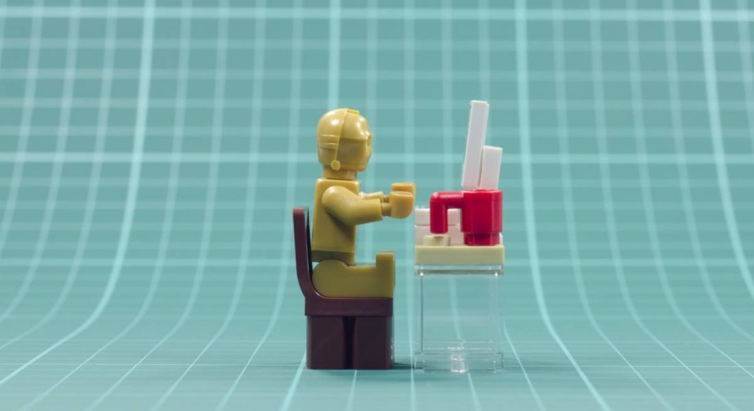 A close-up of a toy lego robot sitting at a tiny toy desk on a sloping turquoise grid background.