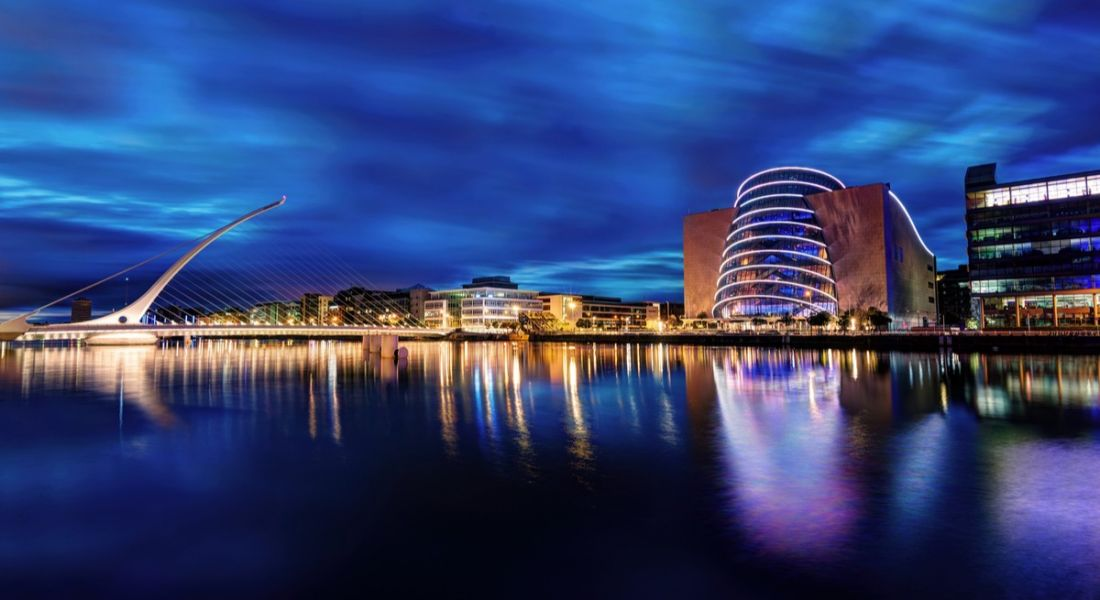 A view of the River Liffey with the white, arching Samuel Beckett Bridge and the cylindrical Convention Centre in Dublin.