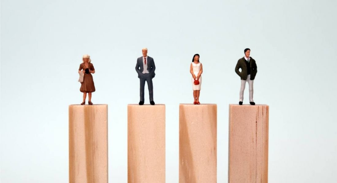 Four small figurines of women and men stand atop wooden platforms of equal height
