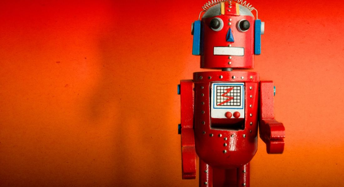 A red toy robot facing the camera. It is standing against an orange-red background.