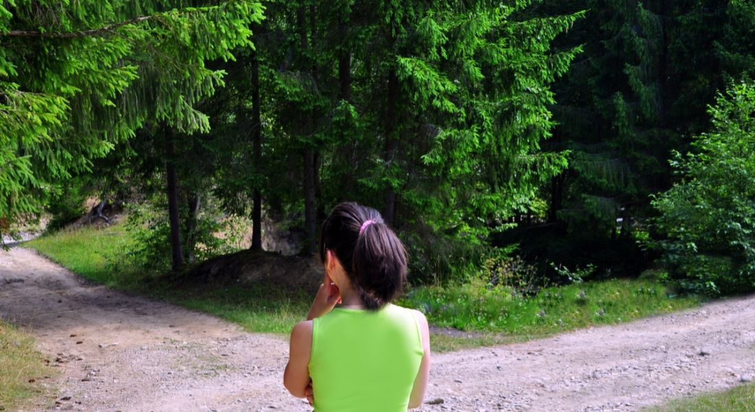 Young woman standing at fork in the road.