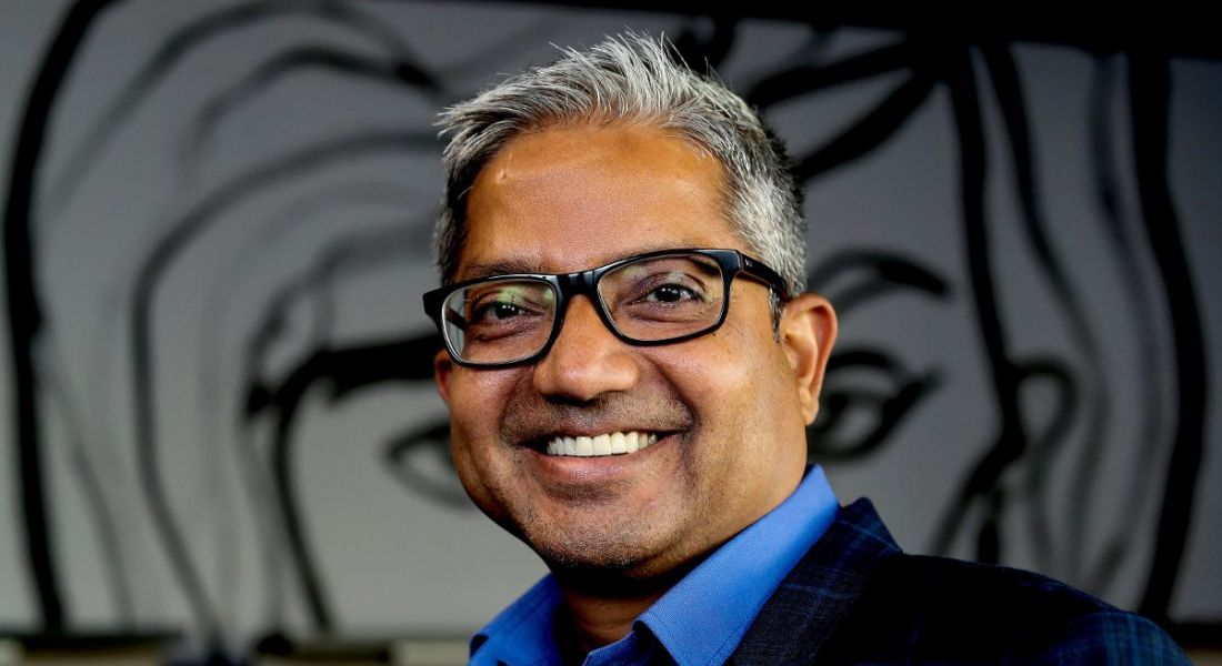 An Indian man with thick-framed glasses and silver stubble flashes a toothy smile at the camera against a grey background.