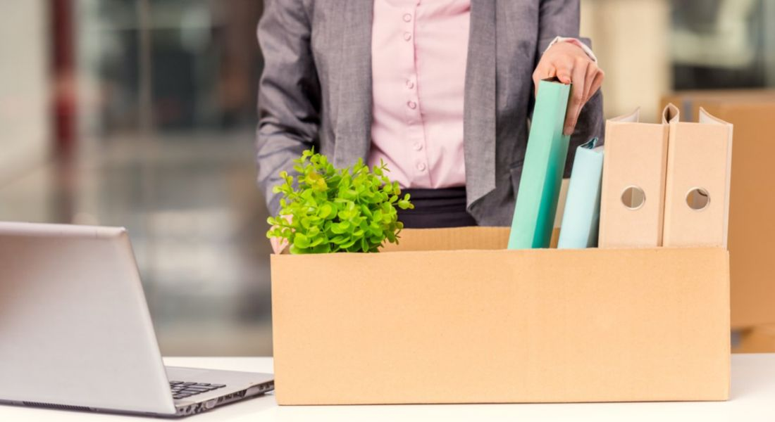 A woman packing her desk items into a box beside a laptop. She's moving to a big company from a small one.