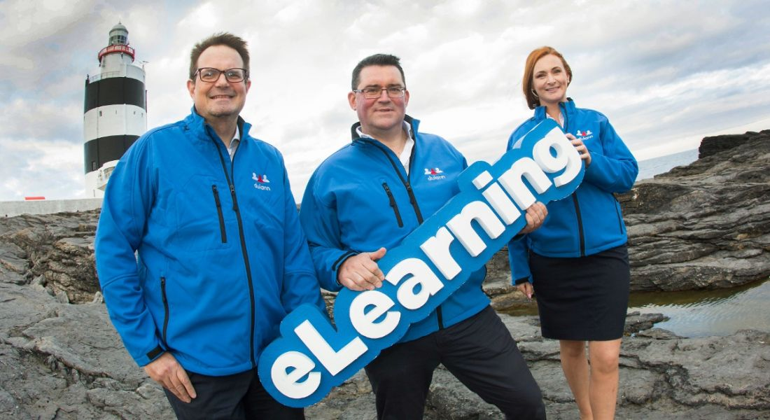 Three people in electric blue windbreakers holding a sign that says 'eLearning'. On a rocky shore with a lighthouse visible behind them.