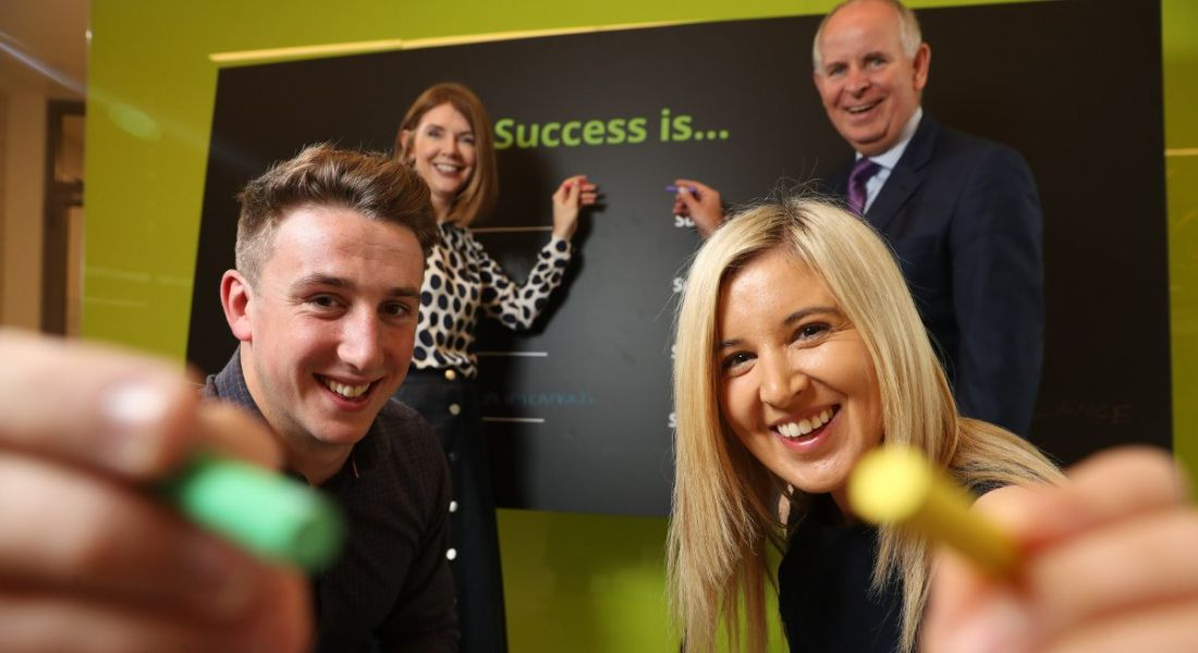 Two young graduates in foreground hold pieces of chalk while two older professionals point to a blackboard in the background.