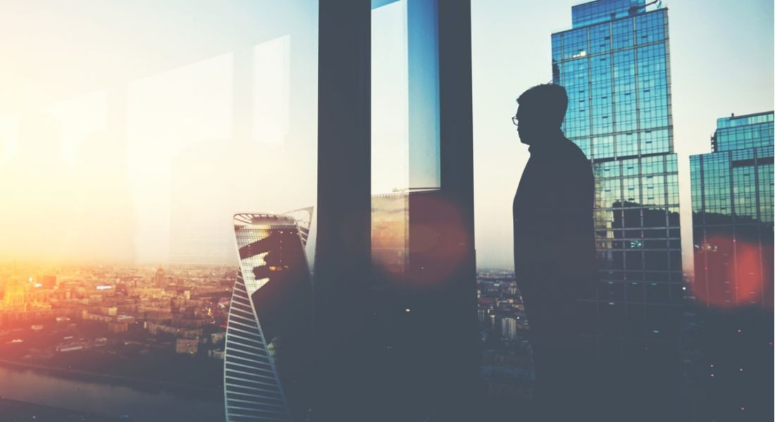 A silhouette of a man thinking about the future of work on a balcony looking out at a cityscape, with the sun rising.