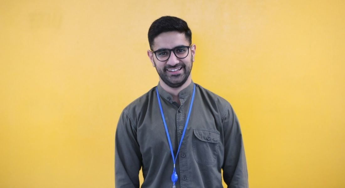 A smiling dark-haired man with a beard and glasses against a yellow background. He's wearing a casual shirt and blue lanyard.