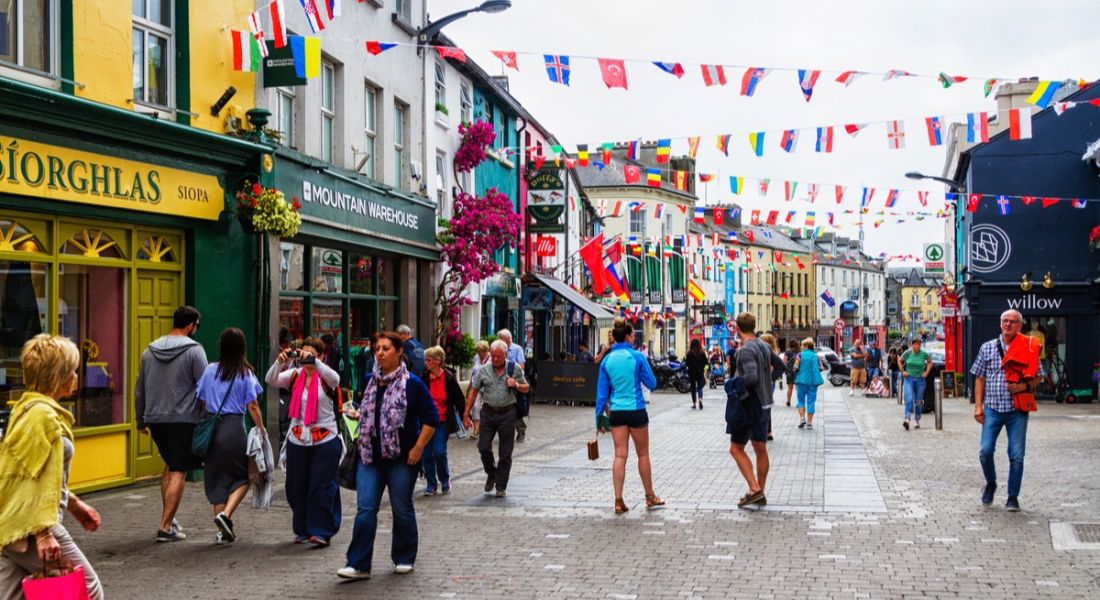 A busy pedestrian street in Galway – where Wayfair is – with bright shopfronts and international flags hanging at the top.
