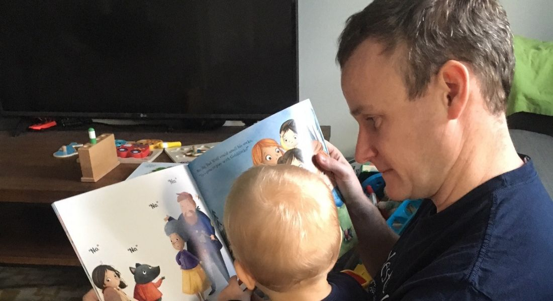 A man with short brown hair reading a children's book to his toddler on paternity leave. The boy has his back to the camera.