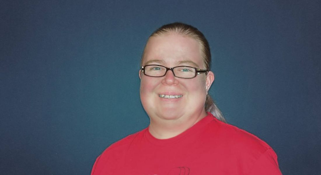 A woman with blonde hair tied back, wearing black glasses and a red t-shirt smiling at the camera against a navy background.