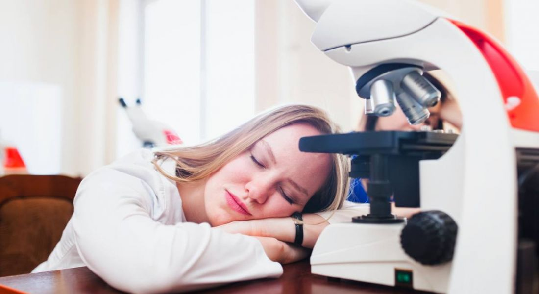 Blonde woman in a lab coat, napping on her desk in front of a microscope. She is stuck in a rut in her life sciences career.