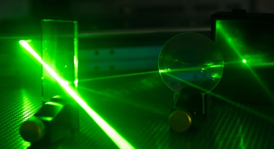 Green laser on optical table in a quantum optics laboratory showing a potential career in photonics.