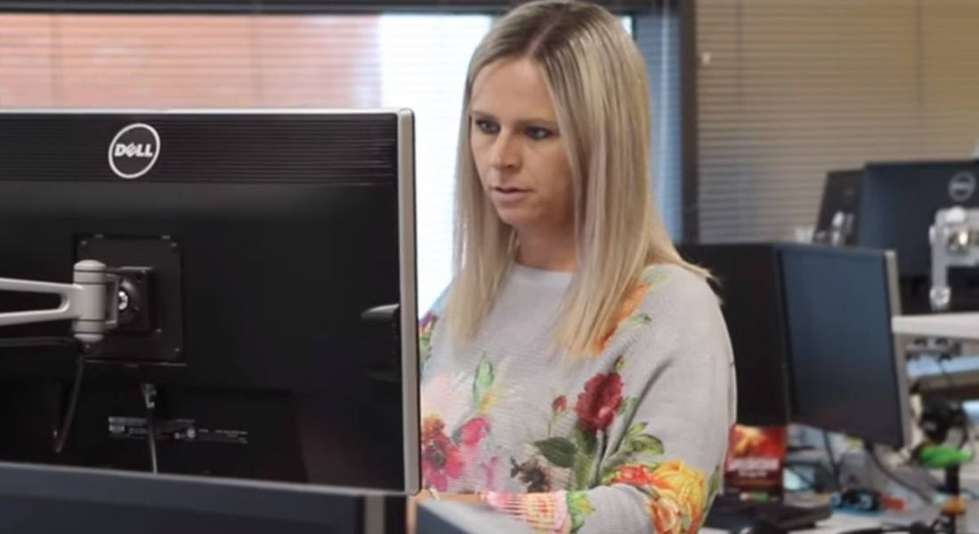 Blonde woman in a flowery jumper working at a computer in the Liberty IT offices.
