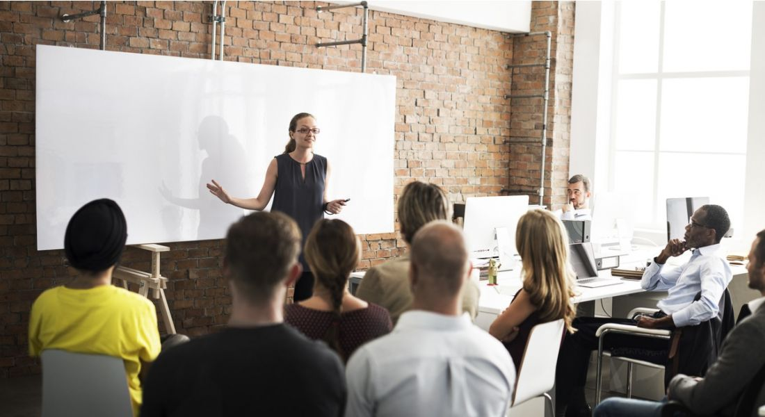 A woman standing in front of a seated crowd of professionals who are there for training. There's a whiteboard behind her.