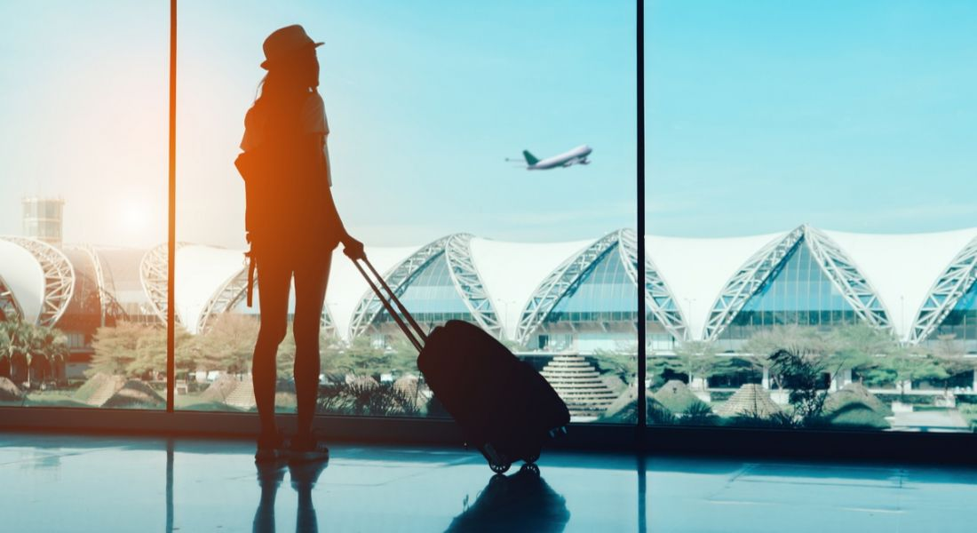 Silhouette of a woman holding a suitcase while looking out the window at an airport terminal watching a plane fly off.