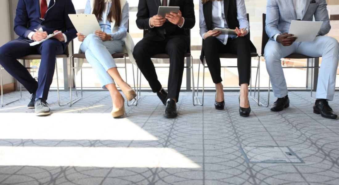 A group of young people sitting in a waiting room waiting to go into a job interview, part of tech recruitment process.